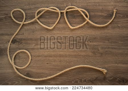 Two heart shapes from rope knot on the wooden panel