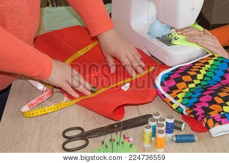 Sewing machine.sewing process in the phase of overstitching. Dressmaker work on the sewing machine. Tailor making a garment in workplace. Hobby sewing fabric as a small business concept