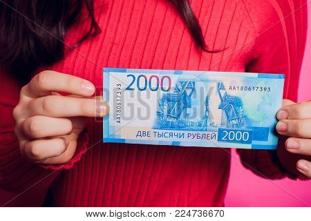 New russian bank notes with Vladivostok images on it. 2000 rubles denomination in woman's hand. colored sweater