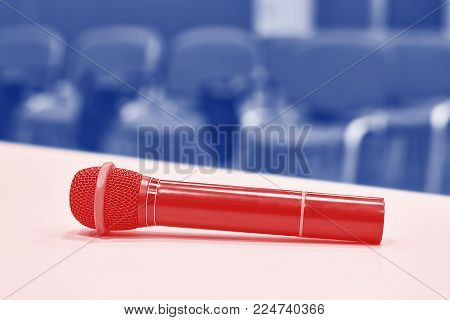 Red microphone on the table in empty auditorium toned
