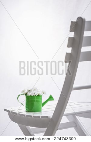 Daisies in watering can on a chair and white curtains -  Bouquet of white delicate daisies in a green watering can on a white wooden chair, in front of a window with white curtains.