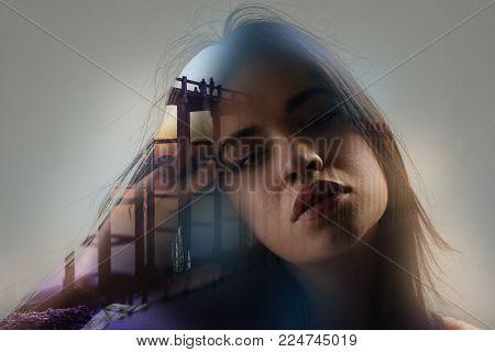 In my head. Creative beautiful sad girl tilting head right holding hand near head and looking straight.