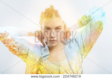 Cute thoughtful colorful girl spending time in the specious room looking straight holding hands behind head.