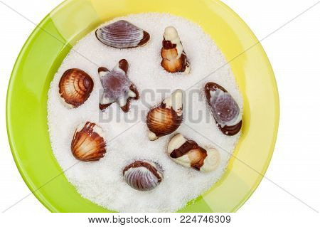 Chocolate sweets in a plate with sugar, isolated on a white background with clipping paths