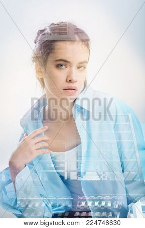 Young beautiful pleasant girl tilting head left holding hand near her neck looking straight.