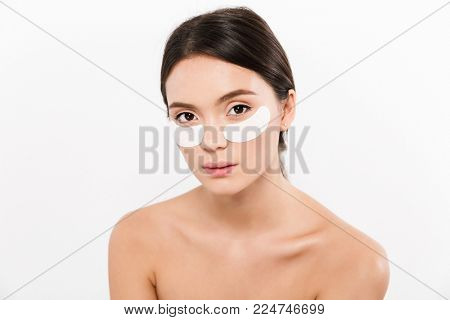 Beauty portrait of healthy shirtless woman with brunette hair wearing cosmetic patches under both eyes isolated over white background