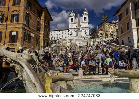 Rome, Italy - September 15 2017: Trinita dei Monti church next to the Spanish Steps with crowd. The church of the Santissima Trinita dei Monti viewed from Fontana della Barcaccia at Piazza di Spagna.