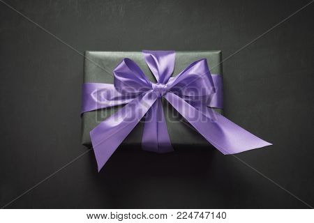 Gift box wrapped in black paper with ultra violet ribbon on black surface. Top view.