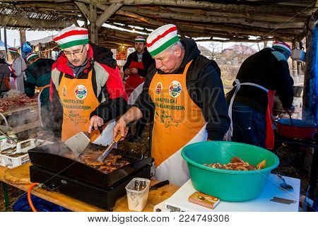 Hecha, Ukraine - January 27, 2018: Hungarian butchers cook fresh national pork dishes on the grill during the 12th International Butchers Festival.