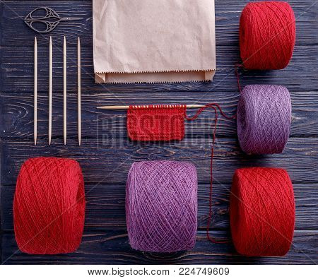 top view of different knitting yarn, knitting needles and knitting accsesories with paper bag on wooden background. Knolling yarn. Flatlay