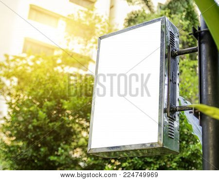 white label board on old square aluminium box of steel circle pole in garden