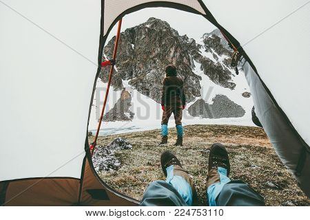 Camping traveling couple view from tent entrance woman walking in mountains man feet relaxing inside Lifestyle concept adventure vacations outdoor