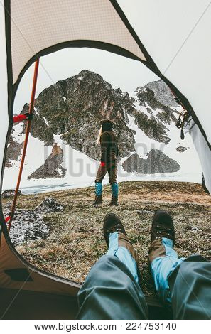 Travel lifestyle camping couple view from tent entrance woman walking in mountains man feet relaxing inside adventure vacations outdoor