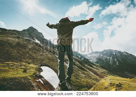 Happy Man raised hands on cliff in mountains Travel Lifestyle emotional concept adventure summer vacations outdoor hiking harmony with nature