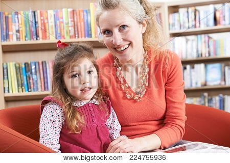 Portrait Of Mother And Daughter Reading Book In Library