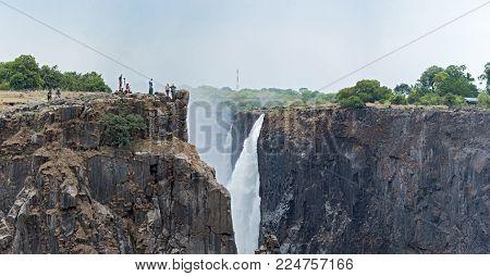 LIVINGSTONE, ZAMBIA-NOVEMBER 23, 2017: Tourists at Victoria Falls, Zimbabwe, Zambia, Africa