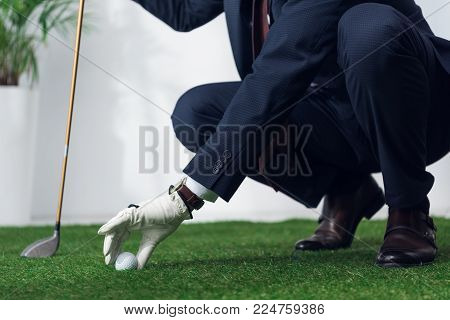 cropped shot of businessman in suit and glove playing golf in office