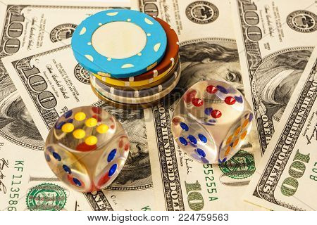 Poker chips and dice on background with american one hundred dollars bills.
