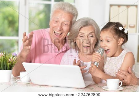Portrait of  happy grandparents  and child singing karaoke