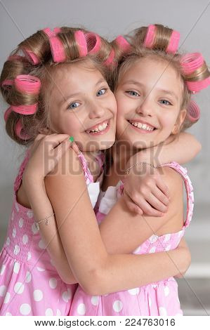 portrait of cute twin sisters with pink curlers hugging