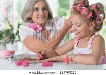 Cute little girl in  hair curlers  with granny beautifying themselves