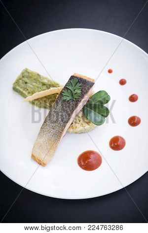 gourmet fusion cuisine salmon fish fillet with guacamole and turmeric rice meal