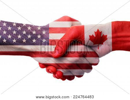 United States and Canada bilateral political relations and cooperation concept with USA and Canadian flags painted on handshake.