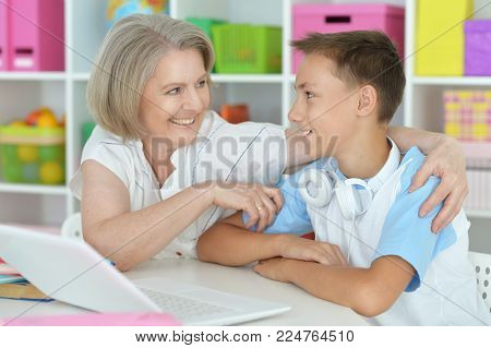 granny with her grandson using laptop at home
