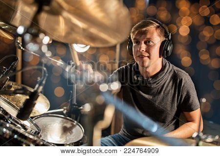 music, people, musical instruments and entertainment concept - male musician or drummer in headphones with drumsticks playing drums and cymbals at concert or studio over holidays lights background