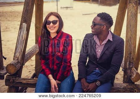 Casual couple sits on swing. Afro american guy and caucasian female on a beach