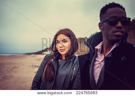 Portrait of afro american guy with caucasian female through wooden columns.