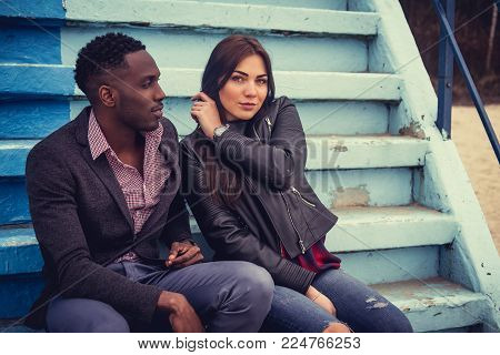 Afro american casual male and caucasian female sitting on concrete steps.