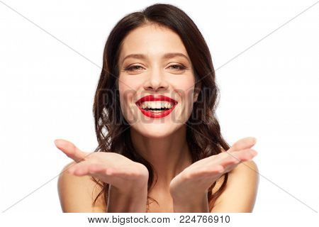 beauty, make up and people concept - happy smiling young woman with red lipstick holding something imaginary on palms over white background