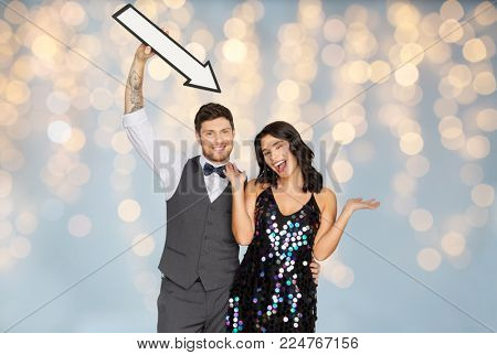 fashion, style and direction concept - happy couple with big arrow at party over festive lights background