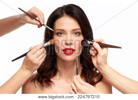 beauty and people concept - beautiful young woman with red lipstick and hands of make up artists with brushes over white background