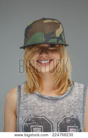 Portrait of positive blonde girl in military cap isolated on grey background.