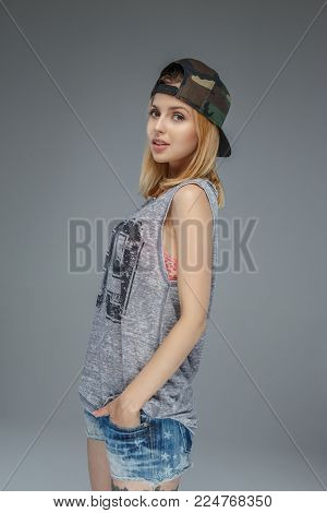 Portrait of positive blonde girl in military cap and denim shorts isolated on grey background
