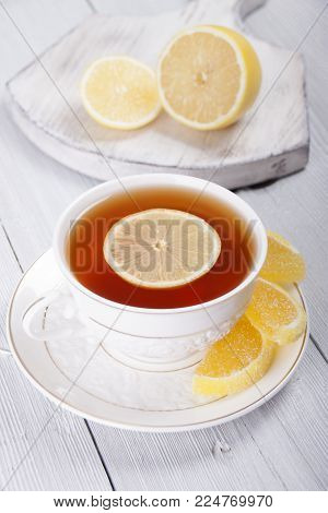 Tea with lemon in a white cup and  marmalade candy in the form of lemon slices in a plate, lemon on a white board