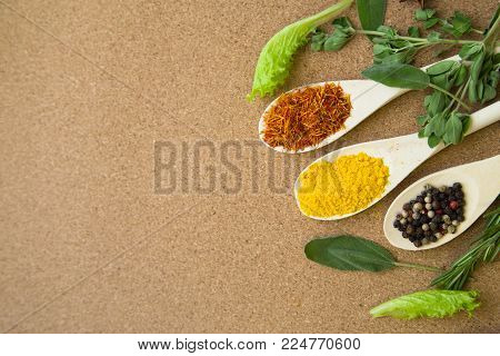Cooking hot spicy meal. A set of spices on wooden spoons: dry salvia, pepper corns and curcuma with fresh herbs on corcwood background, top view