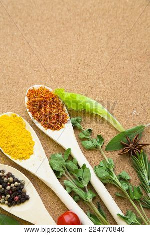 Cooking hot spicy meal. A set of spices on wooden spoons: dry salvia, pepper corns and curcuma with fresh herbs on corcwood background, top view, close up