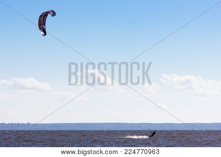 Extreme water sport - kiteboarding at the gulf of finland at summer sunny day