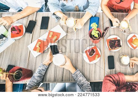 Top view of friends drinking cappuccino at coffee shop restaurant - People having fun together eating cakes and using mobile smart phones at cafe bar - Friendship concept on bright azure filter