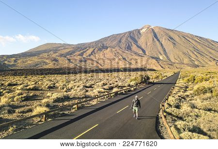Lonely adventure travel photographer walking at Teide National Park in Tenerife - Canarian world famous volcano - Wander concept with world nature wonder with unique wild landscape in Canary Islands