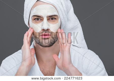 bearded man in bath robe and towel with clay mask on face, isolated on grey, skin care concept
