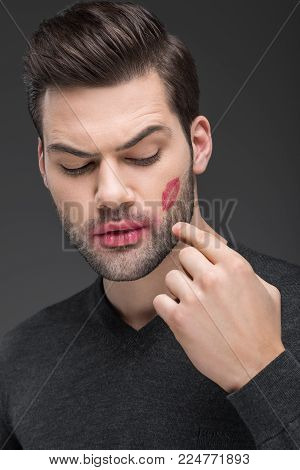 handsome bearded man with kiss print on cheek, isolated on grey poster