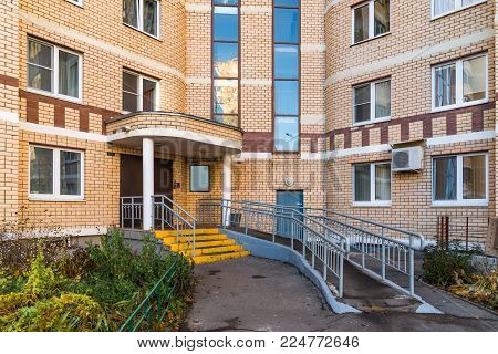 Entrance to a modern high-rise building made of bricks.