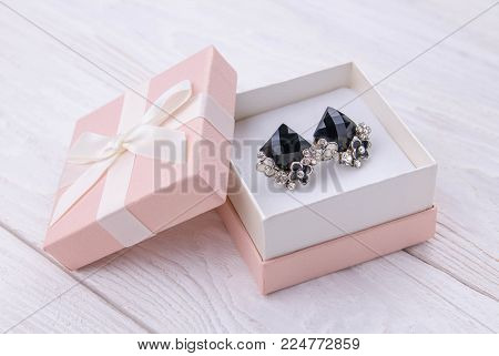 Gold earrings with onyx in the gift box on white wooden background
