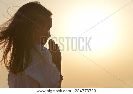 Portrait of little girl praying on light background