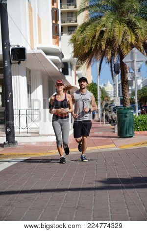 Couple of joggers running together in the street