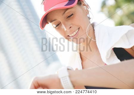 Portrait of jogger woman looking at smartwatch